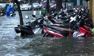 [Video] Hà Nội: Nhiều tuyến phố ngập sâu, người dân bì bõm dắt xe máy lội nước