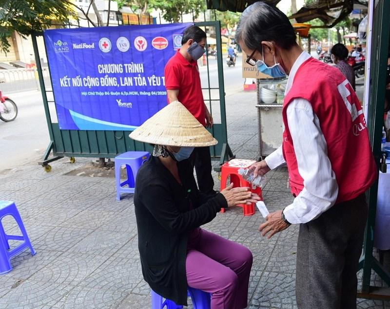 Người dân được rửa tay sát khuẩn và đo thân nhiệt khi đến nhận quà tại Trung tâm Hội Chữ thập đỏ Q.6 sáng ngày 7/4. Ảnh NVL