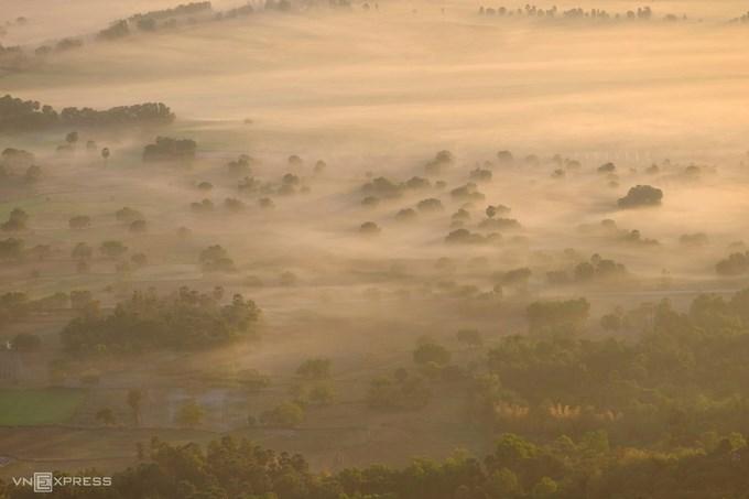 Nắng ửng vàng lúc bình minh hòa cùng làn mây chầm chậm trôi trên những cánh đồng. Ảnh: Nguyễn Đức.
