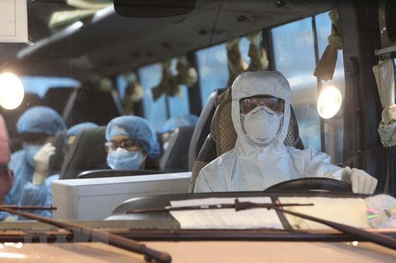 Xe đưa các công dân Việt Nam rời sân bay Vân Đồn đến khu vực cách ly để theo dõi và điều trị. (Ảnh: Dương Giang/TTXVN)
