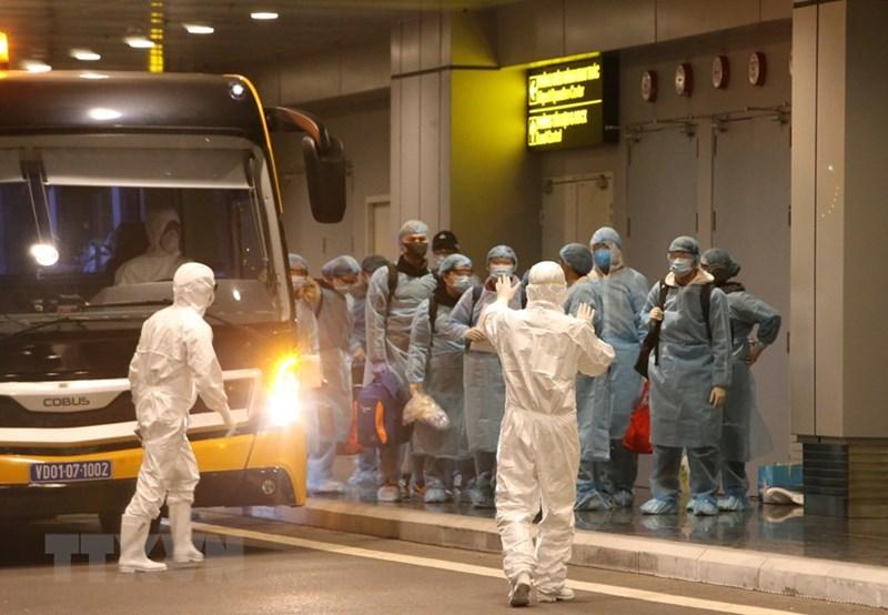 Lực lượng chức năng tại hiện trường hướng dẫn các công dân kiểm tra y tế và làm thủ tục nhập cảnh. (Ảnh: Dương Giang/TTXVN)