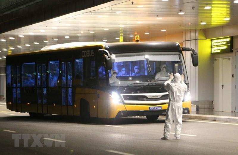 Xe buýt chở 30 công dân Việt Nam từ máy bay vào khu vực khử trùng và làm thủ tục nhập cảnh. (Ảnh: Dương Giang/TTXVN)