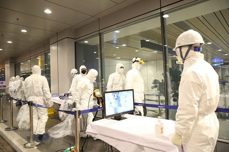 Kiểm tra thân nhiệt, khử trùng người và phương tiện trước khi làm thủ tục nhập cảnh. (Ảnh: Dương Giang/TTXVN)