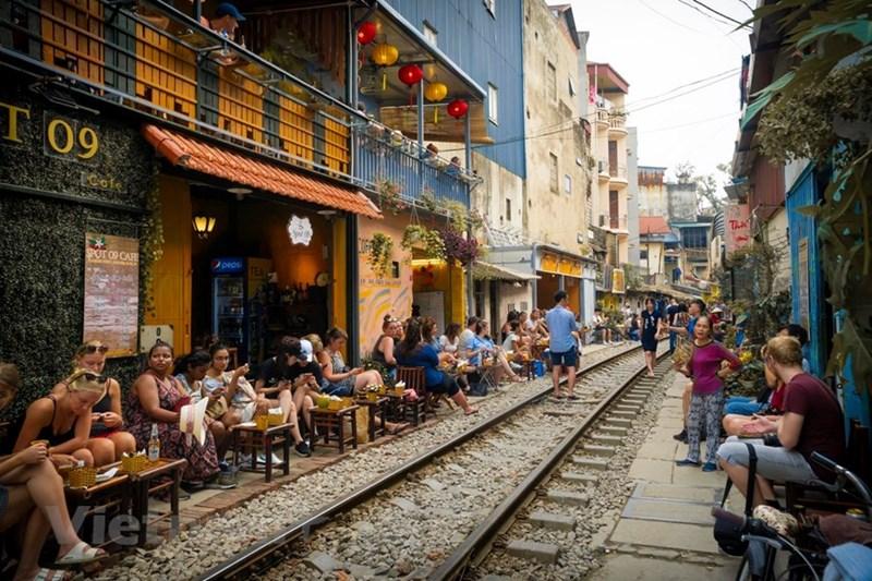 Đoạn đường sắt từ ngã tư giao cắt với phố Điện Biên Phủ đến Phùng Hưng (Hà Nội) tập trung khá nhiều nhà dân. Vài tháng trở lại đây, khu vực này mọc lên hàng loạt quán cà phê nằm sát bên đường ray xe lửa, trở thành điểm hẹn của các bạn trẻ và du khách nước ngoài với mong muốn được trải nghiệm cuộc sống của người dân sống hai bên đường tàu, ngắm cảnh tàu hỏa chạy xuyên qua lòng phố cổ. (Ảnh: Minh Hiếu/Vietnam+)
