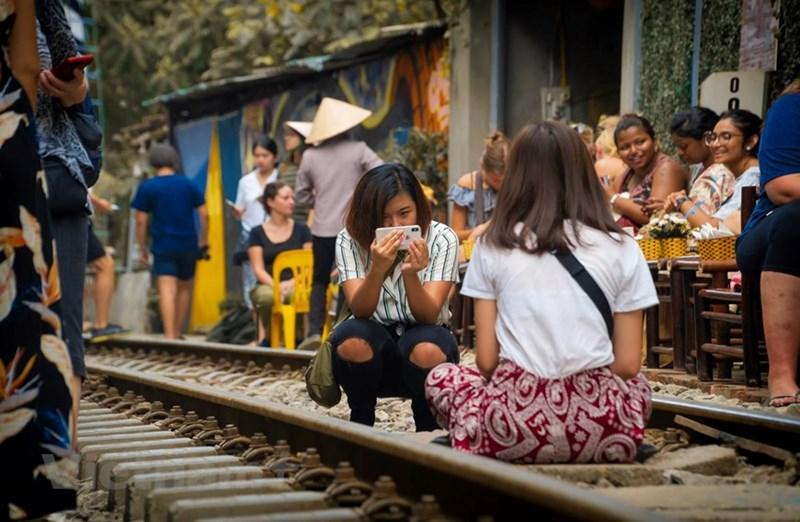 Việc ngồi ăn uống, check in chụp ảnh giữa đường ray thế này rất nguy hiểm. Tuy nhiên với một số người đó lại là một trải nghiệm. (Ảnh: Minh Hiếu/Vietnam+)