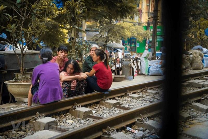 Dọc hai bên đường tàu, xen lẫn với hàng quán đông đúc là nhà của người dân. Hàng ngày, cuộc sống sinh hoạt của họ vẫn diễn ra trên đường ray này. (Ảnh: Minh Hiếu/Vietnam+)