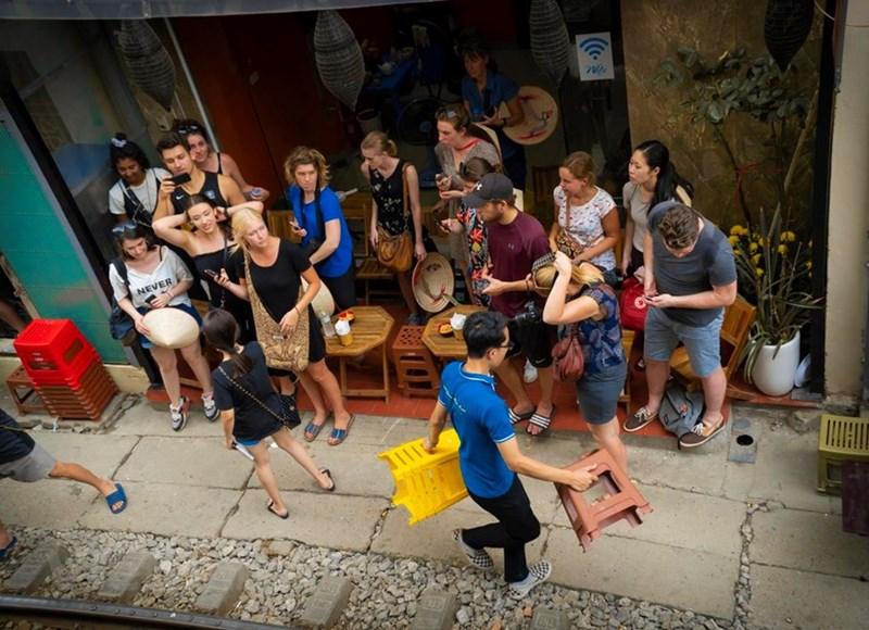 Mỗi khi có đoàn tàu sắp chạy qua trước vài phút, các chủ quán cà phê sẽ hớt hải 'chạy đôn chạy đáo' thu dọn bàn ghế, nhắc nhở khách sẵn sàng tinh thần để 'né' tàu. (Ảnh: Minh Hiếu/Vietnam+)