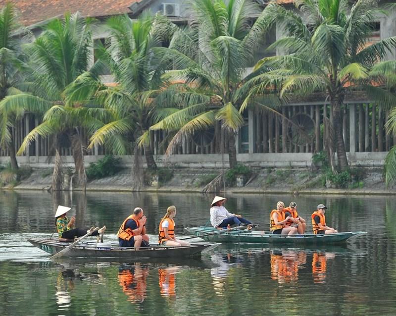Du khách nước ngoài thích thú khi tham quan Tam Cốc bằng thuyền. (Ảnh: Minh Đức/TTXVN)