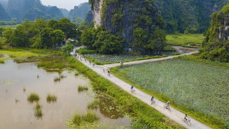 Du khách tự đạp xe khám phá cảnh vật Tam Cốc đầy thơ mộng, cảm tưởng như lạc vào chốn tiên cảnh khi xung quanh là núi cao, sông nước bao phủ. (Ảnh: Minh Đức/TTXVN)