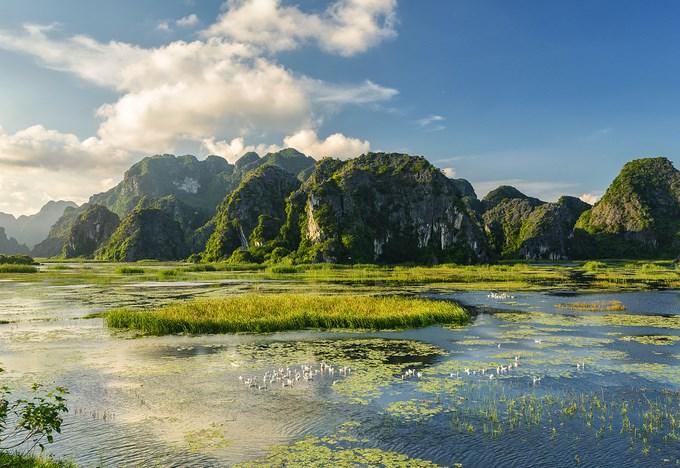"""Cách Hà Nội khoảng 80 km về phía nam, đầm Vân Long được xem là """"vùng đất huyền thoại"""" với khu bảo tồn thiên nhiên đất ngập nước lớn nhất đồng bằng Bắc Bộ. Chỉ cần đứng ngay trên bờ đê, cảnh sắc Vân Long đã hiện ra trước mắt. Xa xa các dãy núi đá vôi sừng sững trông như những hòn đảo chấm phá cảnh sắc thiên nhiên. Mây vờn núi, nước mênh mông phẳng lặng."""