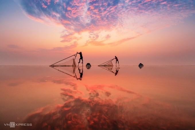 """Tác phẩm """"Bình minh trên biển"""" chụp những người đàn ông đi trên chiếc cà kheo bằng tre cao khoảng một mét, kết hợp với lưới để bắt cá tôm nhỏ tại bãi biển Quang Lang thuộc xã Thụy Hải, huyện Thái Thụy, tỉnh Thái Bình.  Từ bao đời nay, Quang Lang là một làng nghề ven biển, người dân sống chủ yếu bằng nghề khai thác, chế biến thủy sản. Cảnh bắt tôm cá bằng cà kheo trở thành góc ảnh ấn tượng cho các nhiếp ảnh gia."""