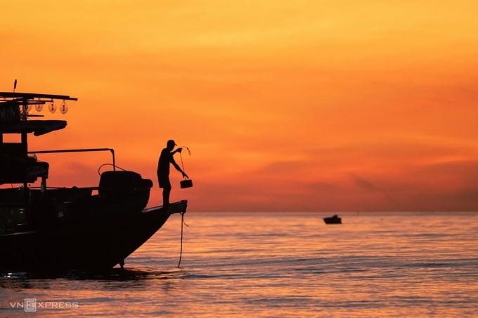 """Bức ảnh """"Buổi sáng trên biển bình minh"""" ở huyện Thăng Bình, Quảng Nam ghi lại nhịp sống của ngư dân trên thuyền trong khung cảnh màu vàng cam lúc rạng sáng."""