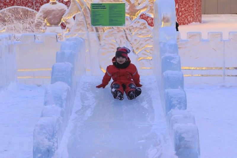 Cây cầu trượt được ghép từ các khối băng để trẻ em vui chơi trong những ngày đông. (Ảnh: Trần Hiếu/TTXVN)