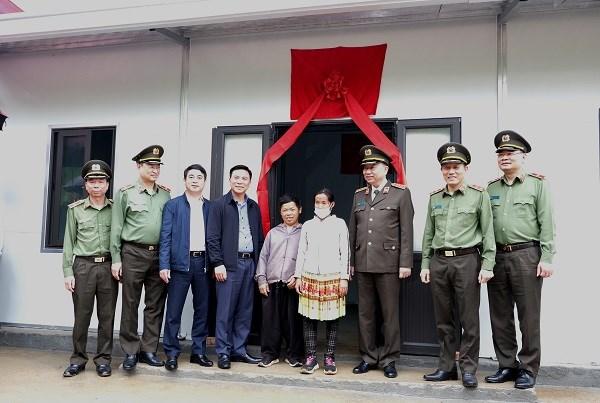 Đại tướng Tô Lâm và đại diện các đơn vị chụp ảnh lưu niệm cùng gia đình anh Vàng A Lồng tại lễ bàn giao nhà tình nghĩa.