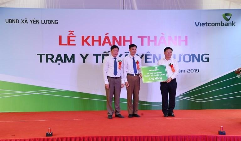 Phó Tổng Giám đốc Vietcombank Đào Minh Tuấn (bên phải) trao tượng trưng số tiền 2 tỷ đồng tài trợ xây dựng Trạm y tế