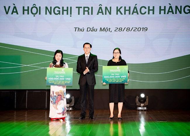 Ông Nguyễn Thái Minh Quang - Giám đốc Vietcombank Bình Dương (thứ hai từ trái sang) trao bảng tượng trưng tài trợ công tác an sinh xã hội cho các đơn vị