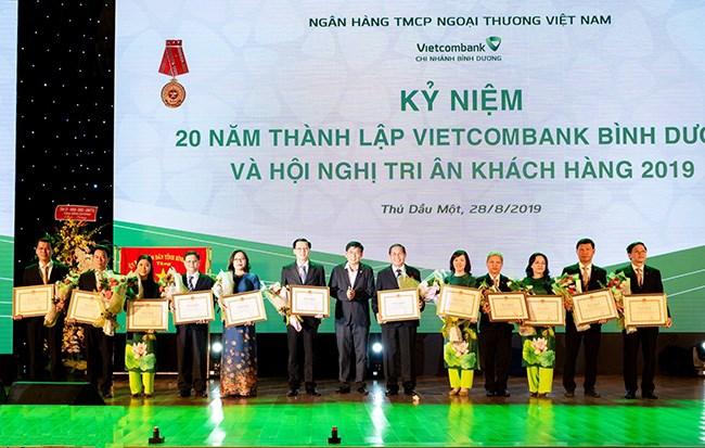 Ông Mai Hùng Dũng - Phó Chủ tịch thường trực UBND tỉnh(thứ 7 từ phải sang) trao Bằng khen cho các tập thể và cá nhân đã có nhiều đóng góp tích cực trong20 năm xây dựng và phát triển Vietcombank Bình Dương