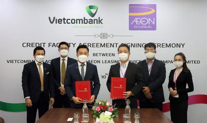Ông Nguyễn Thành Đô–Thành viên HĐQT, Tổng giám đốc Vietombank Lào (hàng đầu bên trái) cùng ông Kunio Kawamura–Giám đốc điều hành AEON Lào (hàng đầu bên phải) thực hiện nghi thức ký kết
