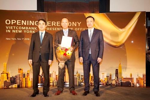 Ông Nghiêm Xuân Thành - Chủ tịch HĐQT (bên trái) và ông Phạm Quang Dũng – Tổng Giám đốc (bên phải) trao quyết định và tặng hoa chúc mừng ông Trần Việt Anh - Phó Giám đốc Công ty TNHH Chứng khoán Vietcombank được điều động và bổ nhiệm Trưởng VPĐD Vietcombank tại Mỹ