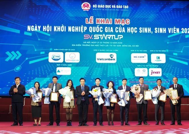 Ông Hồng Quang - Thành viên HĐQT, Giám đốc Khối Nhân sự Vietcombank (thứ 4 từ phải sang) nhận bảng vinh danh nhà tài trợ và hoa chúc mừng từ Ban tổ chức chương trình