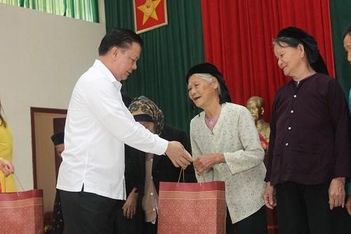 Bộ trưởng Đinh Tiến Dũng trao quà cho đại diện các gia đình chính sách.