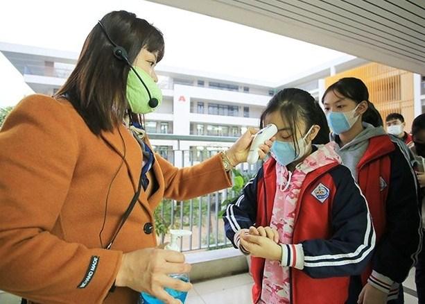 Kiểm tra thân nhiệt là yêu cầu bắt buộc trước khi học sinh vào lớp học.