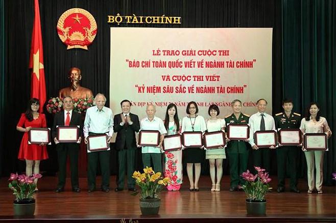 Đồng chí Đinh Tiến Dũng, Ủy viên Ban Chấp hành Trung ương Đảng, Bộ trưởng Bộ Tài chính trao giải cho các tập thể, cá nhân đạt giải báo chí xuất sắc.
