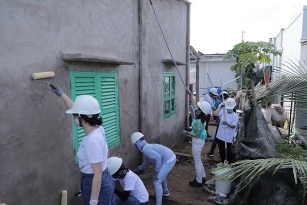 Các tình nguyện viên JTI và đối tác cùng nhau quét vôi cho bức tường tại ngôi nhà ở Tiền Giang.