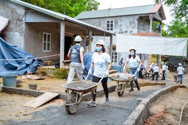 Các tình nguyện viên JTI và đối tác chung tay vận chuyển nguyên liệu để xây dựng ngôi nhà tại Hòa Bình.