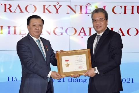 """Thứ trưởng Bộ Ngoại Đặng Minh Khôi trao tặng Kỷ niệm chương """"Vì sự nghiệp ngoại giao Việt Nam"""" cho Bộ trưởng Bộ Tài chính Đinh Tiến Dũng"""