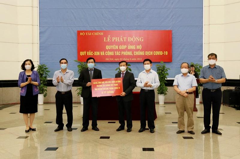 Dưới sự chứng kiến của Bộ trưởng Hồ Đức Phớc và các Thứ trưởng Bộ Tài chính, Chủ tịch Công đoàn Bộ Tài chính Nguyễn Hữu Thân trao 5 tỷ đồng quyên góp, ủng hộ của ngành Tài chính vào Quỹ vắc xin phòng Covid-19.