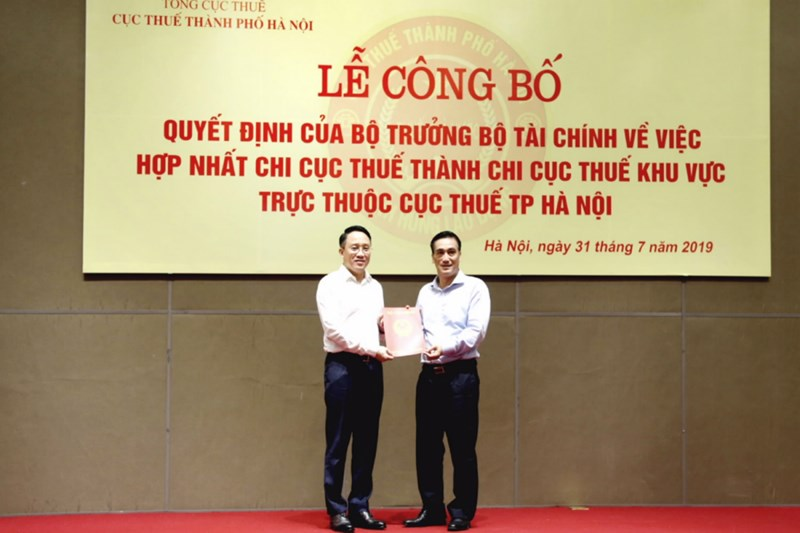 Thứ trưởng Trần Xuân Hà trao Quyết định của Bộ trưởng Bộ Tài chính về hợp nhất Chi cục thuế thành Chi cục thuế khu vực trực thuộc Cục Thuế TP. Hà Nội cho Cục trưởng Cục Thuế Hà Nội Mai Sơn.