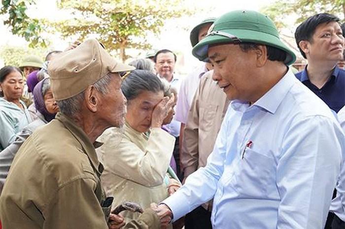 Thủ tướng Nguyễn Xuân Phúc thăm hỏi, động viên người dân bị thiệt hại do mưa lũ tại huyện Quảng Ninh, tỉnh Quảng Bình. Ảnh: VGP/Quang Hiếu