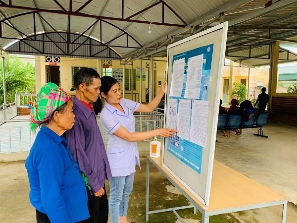 Cán bộ Trạm Y tế xã Phúc Than (huyện Than Uyên, tỉnh Lai Châu) hướng dẫn người dân sử dụng thẻ BHYT