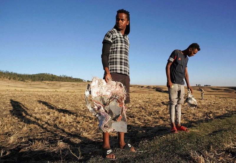 Những người dân ở khu vực máy bay rơi thu dọn các mảnh vỡ của máy bay. Ảnh Jemal Countess/Getty Images
