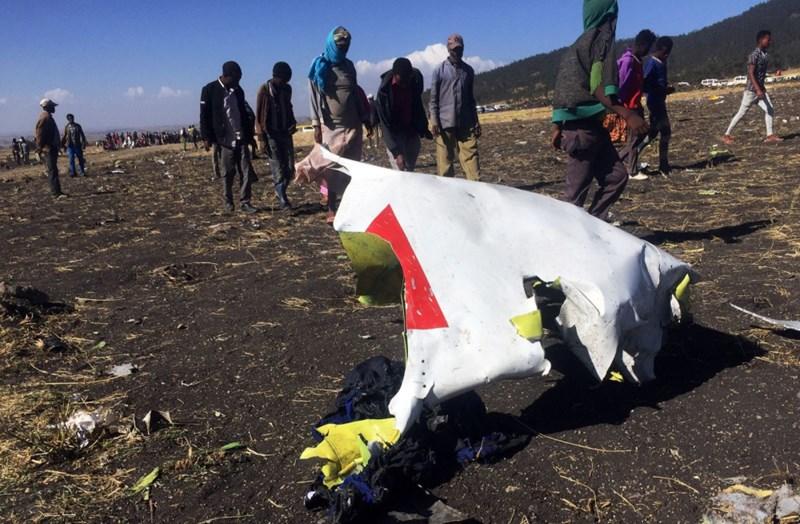 Những người dân đau buồn khi đi ngang qua mảnh vỡ của chiếc máy bay bị nạn. Ảnh TIKSA NEGERI/REUTERS
