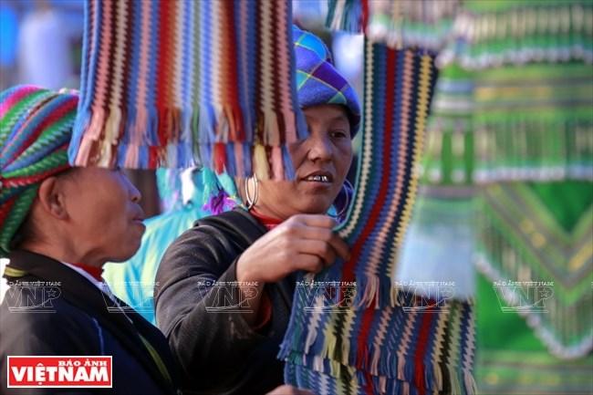 Phụ nữ Mông chọn hàng tại một hàng quần áo ở chợ Y Tý.