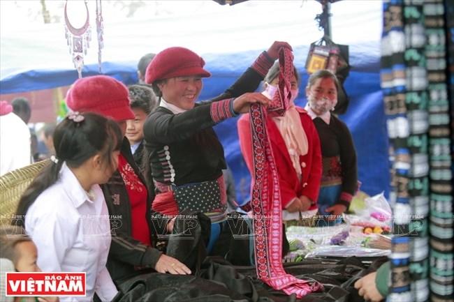 Niềm vui của cô gái người Mông khi chọn mua những dải vải màu.