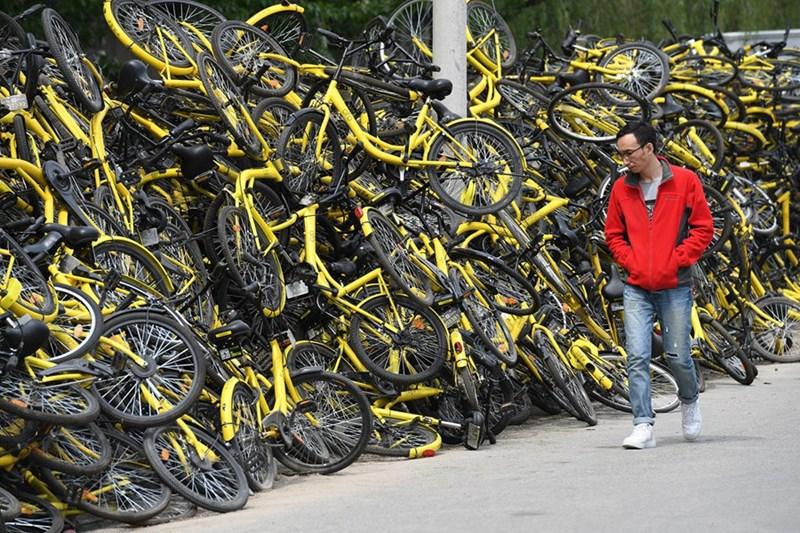 Xe đạp của các hãng chia sẻ chất đống bên ngoài một tiệm sửa xe ở Bắc Kinh.