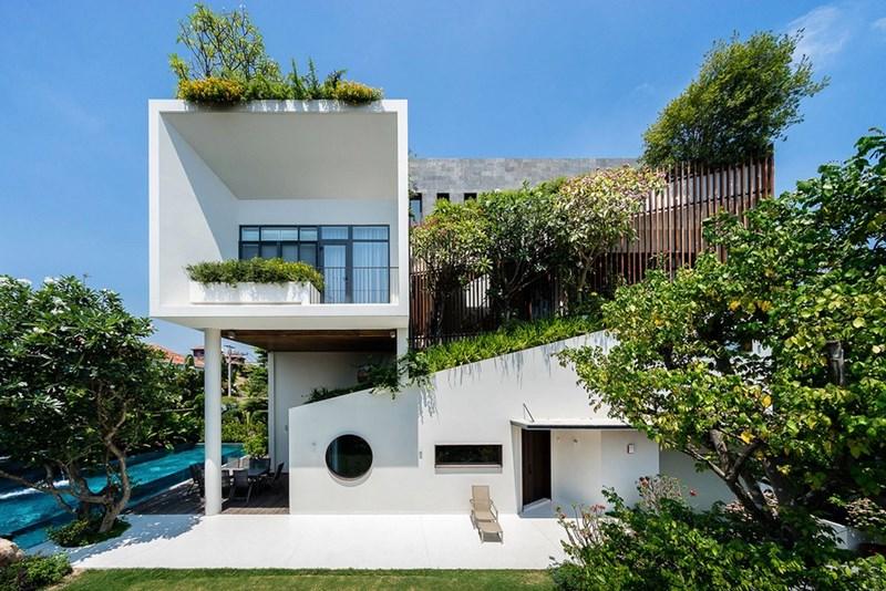 Vẻ ngoài của ngôi nhà như một khối hình học được sắp đặt tự do, chồng lên nhau, nằm trên một tấm vải màu xanh da trời.