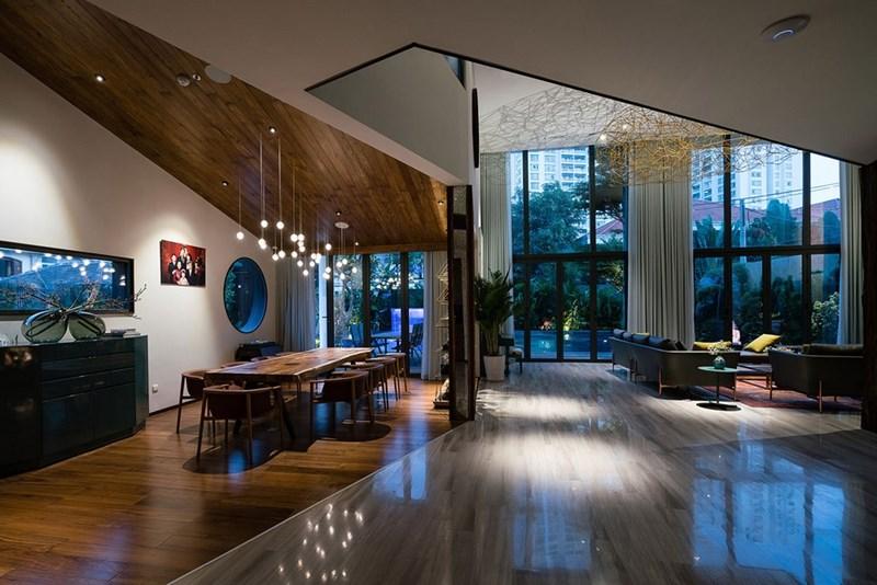 Ngay bên cạnh phòng khách là phòng ăn. Hai không gian được mở thông nhau tạo cảm giác rộng rãi. Hai khu vực được phân chia bằng màu sàn gỗ.