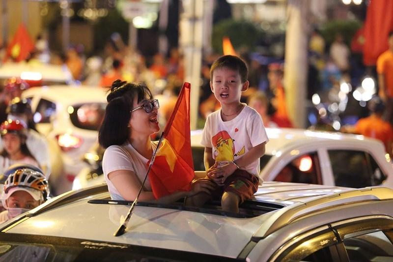 Em nhỏ cùng mẹ hòa vào dòng người ăn mừng chiến thắng Olympic Việt Nam.