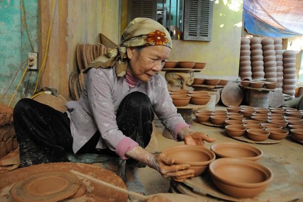 """Theo những """"nghệ nhân tay đất"""": """"Làm gốm ngày trước rất vất vả. Nhiều khi trời rét nhưng vẫn phải lấy tay trộn đất. Các xưởng làm gốm hầu như không có mái che nên những lúc phơi gốm mà gặp trời mưa lại phải chạy ra bê hết vào nhà""""."""